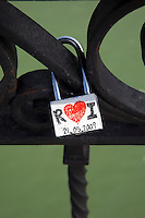 A lovers' pact on a modern padlock and a wrought-iron gate