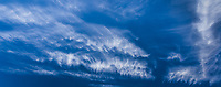 A deep blue sky with wispy white clouds in horizontal panoramic.