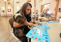 Brenda Keeding checks her bingo cards Monday, July 19, 2021, as her dog Missy Bell, Yorkshire Terrier, at the Fayetteville Senior Activity and Wellness Center. The center offers bingo on Mondays and Thursdays. Check out nwaonline.com/210720Daily/ and nwadg.com/photos for a photo gallery.(NWA Democrat-Gazette/David Gottschalk)
