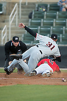 Tyler Sullivan (5) of the Kannapolis Intimidators slides across home plate ahead of the tag attempt by Hickory Crawdads pitcher Brett Martin (31) as umpire Ryan Powers looks on at Kannapolis Intimidators Stadium on April 7, 2016 in Kannapolis, North Carolina.  The Crawdads defeated the Intimidators 5-1.  (Brian Westerholt/Four Seam Images)