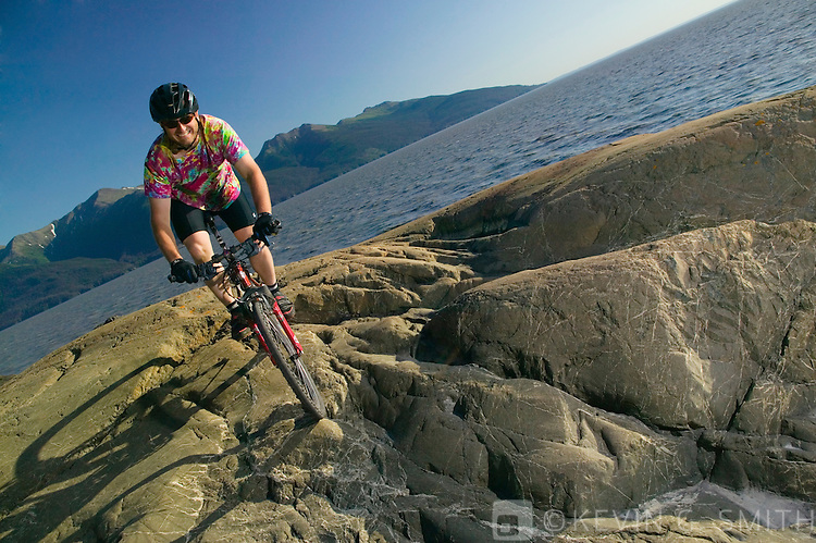 Middle aged man, caucasian, riding a mountain bike on the rocks along the shoreline, Turnagain Arm, Summer, Kenai mountains in the background, Southcentral Alaska, USA. MR.