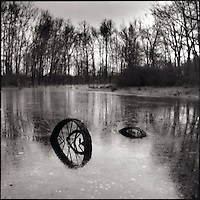 Farm tractor wheel in iced pond<br />