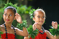 Two young girls wearing red dresses and kukui nut leis dancing hula.
