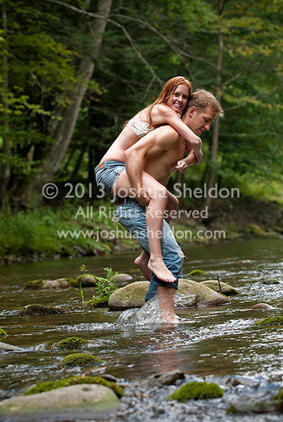 Young man giving piggy back ride to young woman in stream