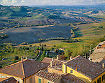 Tuscany, Italy       <br /> Tiled roofs of Montepulciano with farms, green fields and vineyards in the valley below