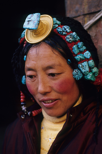 Portrait of a Tibetan woman (pilgrim) with traditional jewelry at the Jokhang Temple in Lhasa, Tibet, China.