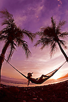 A girl with hat reclines in a hammock on Maui's west side at sunset.