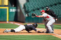 Joe Davis (44) of the Houston Cougars waits for a pick-off throw as Tyler Neslony (10) of the Texas Tech Red Raiders dives back into first base at Minute Maid Park on February 26, 2016 in Houston, Texas.  The Red Raiders defeated the Cougars 3-2 in game one of the 2016 Shriners Hospitals for Children College Classic.  (Brian Westerholt/Four Seam Images)