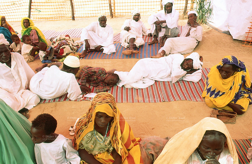 Sudan. West Darfur. Kerenek. The non-governmental organization (ngo) Médecins sans Frontières (MSF) Switzerland runs a medical program. A group of women, wearing a veil on their heads, and men, dressed in white clothes and a turban on the head, wait for a medical consultation with a doctor. © 2004 Didier Ruef
