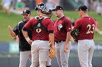 Pitching coach Marc Valdes (17) of the Savannah Sand Gnats, in the black pullover, shouts at umpire George Reidel during a game against the Greenville Drive on Sunday, August 24, 2014, at Fluor Field at the West End in Greenville, South Carolina. Valdes was ejected, and Greenville won, 8-5. (Tom Priddy/Four Seam Images)