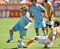 Colorado Rapids defender Jordan Harvey (2) is slide tackled by Houston Dynamo midfielder Brian Mullan (9).  Houston Dynamo defeated Colorado Rapids 1-0 at Robertson Stadium in Houston, TX on April 19, 2009.