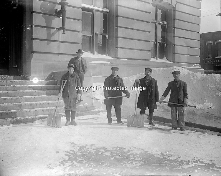 SNOW SHOVELERS AT THE POST OFFICE. John Johnson was listed in city directories as a laborer or janitor at the post office on and off from 1904 to 1917. When he resigned in 1917, his pay was $600 per year. He often photographed his workmates, here taking a break from shoveling a deep snowfall. They stand outside the south entrance, which was in-filled with a window in the remodeling and extension of 1914-1916.<br /> <br /> Photographs taken on black and white glass negatives by African American photographer(s) John Johnson and Earl McWilliams from 1910 to 1925 in Lincoln, Nebraska. Douglas Keister has 280 5x7 glass negatives taken by these photographers. Larger scans available on request.
