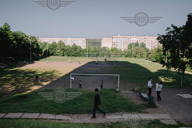A couple stand with a baby beside a football pitch, where a group of children are playing, in the Ciocana district.