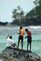 Three young boys fishing from the rocks Bocas Del Toro, Panama