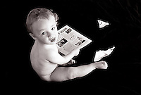 Nine month old baby boy looking at camera and playing with a magazine while naked.