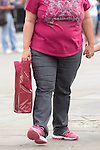 Overweight fat obese mother holding daughters hand London UK