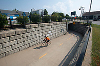 A cyclist riding on the Razorback Greenway exits the tunnel under MLK Blvd. near the South Yard development Thursday Sept. 2, 2021 in Fayetteville. The city wants to  expand the boundary for the Outdoor Refreshment Area to the South Yard development area and lift its expiration date. Visit nwaonline.com/210000906Daily/  (NWA Democrat-Gazette/J.T. Wampler)