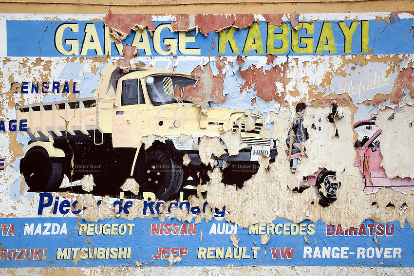 Rwanda. Southern province. Kabgay. District of Muhanga. Giant advertisement board for a garage. Torn poster. Repair service by professional cars mechanics on various brands, Peugeot, Renault, Range-Rover, Audi, VW, Mercedes,... © 2007 Didier Ruef