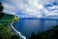 Beautiful scenic view of Waipio Valley with it black sand beach, clouds, blue sky and blue water.