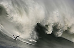 A surfer slides off his board trying to hold on after writing a giant wave at the Mavericks competition in Half Moon Bay.