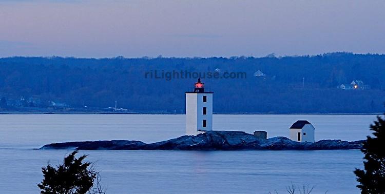 The Dutch Island Light glows as night approaches.