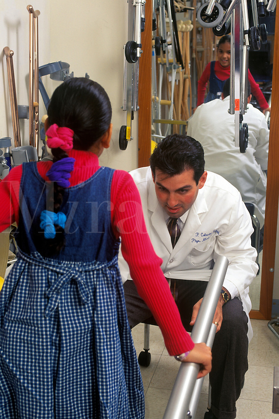 Physical medicine doctor evaluates and encourages young patient.