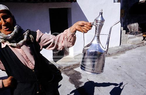 Sarajevo, Bosnia. Old woman with muslin headscarf selling a tin Turkish coffee pot in the street.