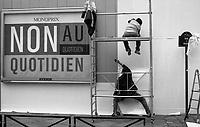 Paris (île de france)<br /> <br /> Hommes en train de travailler a cote d`un panneau publicitaire de monoprix.<br /> <br /> Men working beside a billboard `s monoprix.