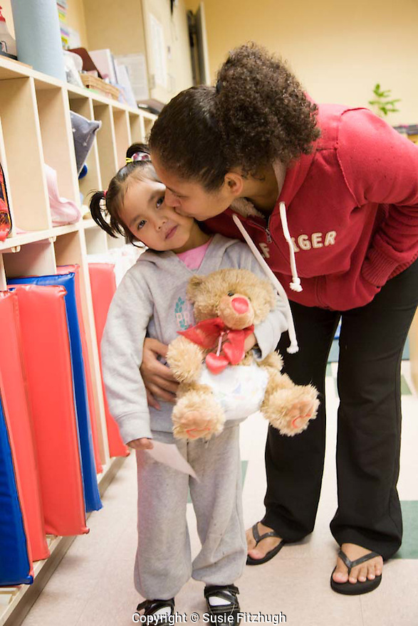 New child arrives at daycare site and allows her mother to kiss her goodbye.