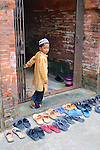 Built in the 15th century, the red brick mosques of Bagerhat are still in use by local people. A young boy slips off his shoes to join in midday prayers at Bibi Begni mosque.