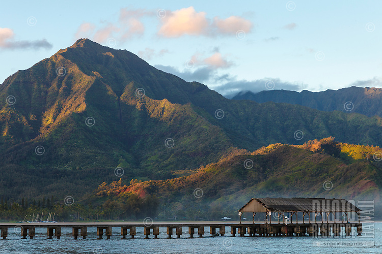 At dawn, a couple at the end of Hanalei Pier take in the view of Hanalei Bay, Kaua'i.