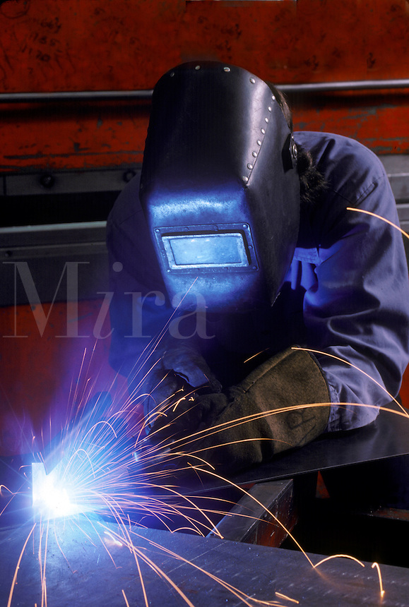 A welder wearing a protective face mask at work.