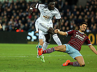 Pictured L-R: Bafetimbi Gomis of Swansea has his shot stopped by a West Ham defender Saturday 10 January 2015<br /> Re: Barclays Premier League, Swansea City FC v West Ham United at the Liberty Stadium, south Wales, UK