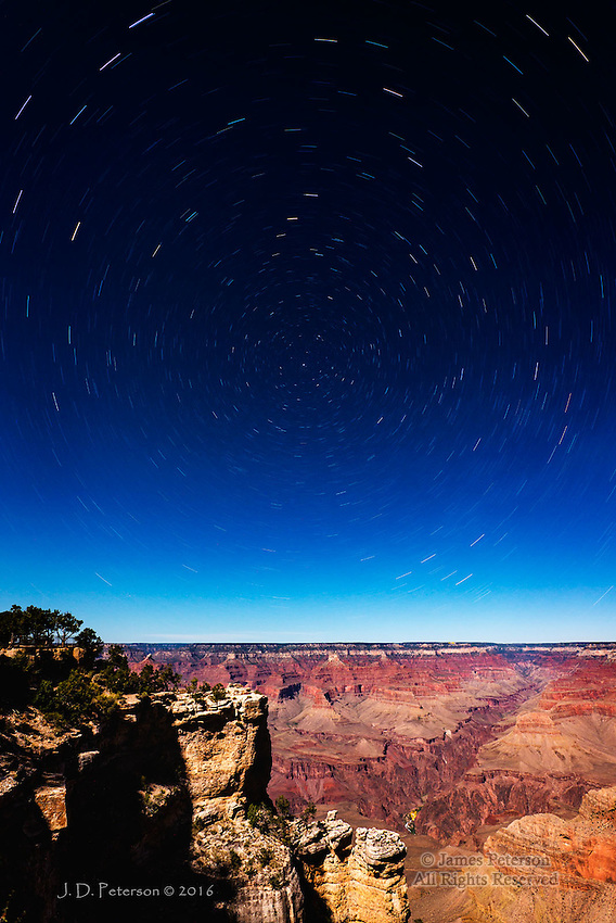 """Grand Canyon by Moonlight ©2016 James D. Peterson.  The moon was at about half phase when I made this 16 minute exposure from near Mather Point on the South Rim.  That provided plenty of illumination to capture the depths of the canyon, including the lights of Phantom Ranch at the bottom of the canyon about a mile below my position.  The stars are stretched by the long exposure into star trails rotating around Polaris (the North Star).  The Big Dipper can be seen in the upper left, and Casseopoeia (the big """"W"""") is in the lower right."""