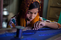 """Sumaiya* is 15 years old and lives with her parents, brother and sister in a slum in Dhaka, Bangladesh. She attends school but also works about 2 hours daily at home doing ornamental stitching, flower chains and dress decorations. Through this work she and her mother contribute to the family income. """"I started working when I was 11"""", tells Sumaiya*. """"The salary is not very good, but I can keep going to school and help my family with this extra income."""" Sumaiya* doing ornamental stitching in the 1-bedroom house where the whole family lives."""