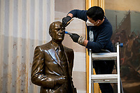 A man works on cleaning up a statue of former President Gerald Ford in the Rotunda at the U.S. Capitol in Washington, DC, Tuesday, January 12, 2021. Credit: Rod Lamkey / CNP /MediaPunch