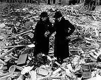 Two bewildered old ladies stand amid the leveled ruins of the Almshouse which was Home; until Jerry dropped his bombs.  Total war knows no bounds.  Almshouse bombed Feb. 10, Newbury, Berks., England.  February 11, 1943.  Naccarata. (Army)<br /> Exact Date Shot Unknown<br /> NARA FILE #:  111-SC-178801<br /> WAR & CONFLICT BOOK #:  1261