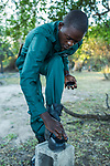 Anti-poaching scout cleaning shoes before deployment, Kafue National Park, Zambia