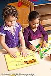 Education preschool 3 year olds two girls playing side by side with puzzles separately vertical