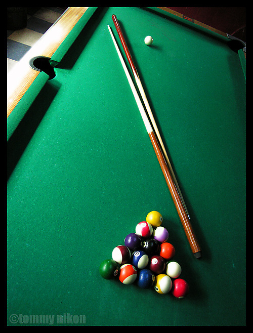 Pool table with cue sticks and racked balls