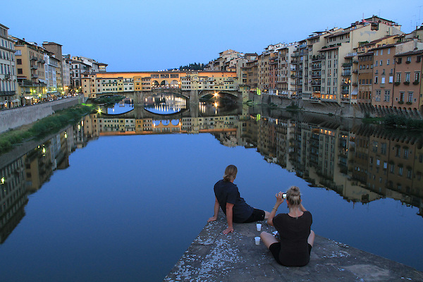 Italy, Florence.  When the Facts Change, I Change My Mind.<br /> I came to this spot with a classic cityscape in my mind, one at sunset with the city lights coming on. When this couple showed up (and wouldn't leave), I changed my mind.<br /> Couple enjoying drinks and a sunset over the Arno River, Florence, Italy.