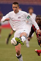 New England Revolution's Brian Kamler is watched by the MetroStars' Fabian Taylor The New England Revolution played the NY/NJ MetroStars to a 1 to 1 tie at Giant's Stadium, East Rutherford, NJ, on April 25, 2004.