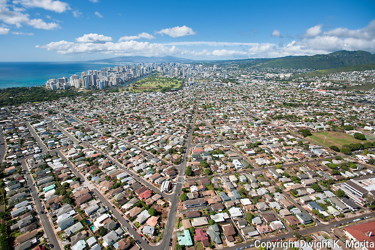 Homes and businesses fade into a skyline of high-rise buildings and hotels as you approach Waikiki from the east.