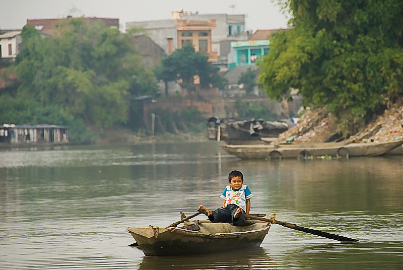 Young Vietnamese boy paddles to houseboats along the river just outside of Hanoi, Vietnam