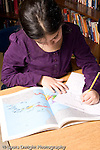 Elementary school Grade 5 female student working on geography social studies lesson using map vertical