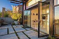 Margarido House, Oakland, California - LEED. Sliding glass doors opening living room to garden patio overlooking San Francisco Bay
