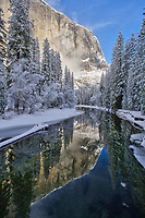 The calm waters of the Merce River reflect the cliffs, clouds and snow-covered trees in Yosemite National Park, California.