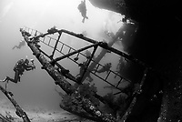 black and white, Ghiannis D. shipwreck being explored by two scuba divers, ship was previously named the Markos D, sunk on April 19, 1983, hit the shallow reef at Sh'ab Abu Nuhas and sunk, Egypt, Red Sea