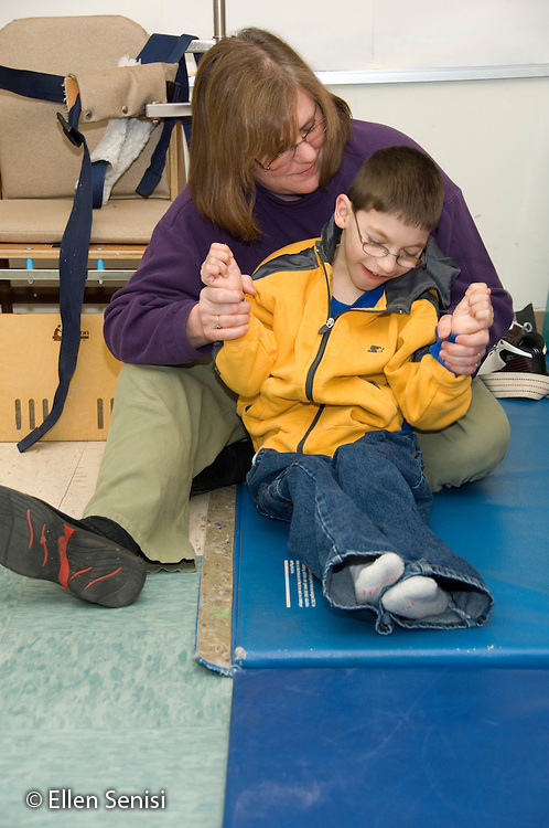MR / Albany, NY.Langan School at Center for Disability Services .Ungraded private school which serves individuals with multiple disabilities.Physical therapist holds childs' arms to help with balance while sitting. Boy: 9, cerebral palsy, limited verbal output with expressive and receptive language delays.MR: Rub1; Tho15.© Ellen B. Senisi