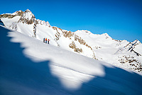 Three ski tourers, framed in shadow, stand looking out at the ski terrain above the Gauli Hut while on the Berner Haute Route, Switzerland.